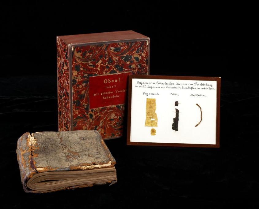 Kodex in Originaleinband inkl. Aufbewahrungsbox für die Handschrift und Infotafel zur verwendeten Bindetechnik